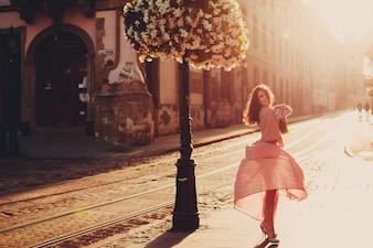 """""""Lächelnde Frau hält Blumen auf der Straße"""""""