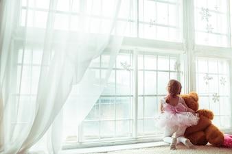 """Mädchen umarmt Teddybär Blick auf Fenster"""