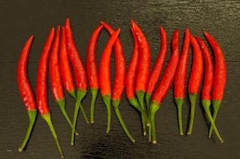Red hot Chili Peppers auf schwarzem Hintergrund aus Holz