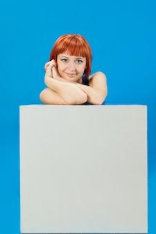 Red Mädchen mit leeren Brett über blauem Hintergrund