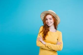 Reise-Konzept - Nahaufnahme Porträt junge schöne attraktive Redhair Mädchen mit trendy Hut und Sonnenbrille lächelnd. Blauer Pastellhintergrund. Platz kopieren