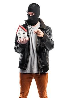 Robber hält ein kleines Haus