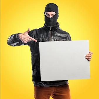 Robber hält ein leeres placard auf buntem hintergrund
