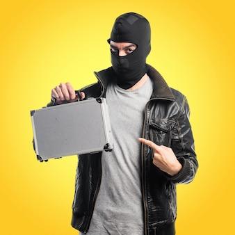 Robber hält eine Aktentasche auf buntem Hintergrund