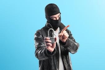 Robber hält Vintage Vorhängeschloss auf bunten Hintergrund