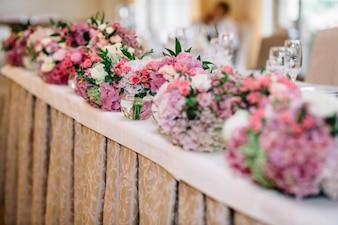 Runde Sträuße von Pastell rosa und grünen Blüten stehen auf lange di