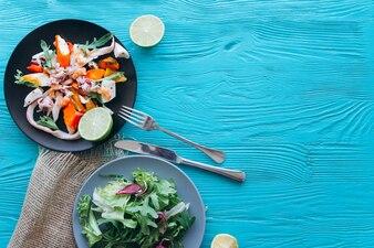 Salat und Nudeln mit Meeresfrüchten auf blauem Hintergrund