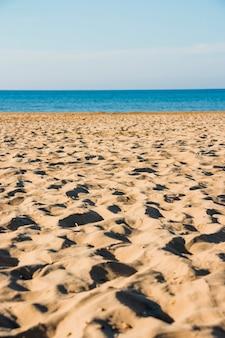 Sandstrand in der Nähe von blauem Meer