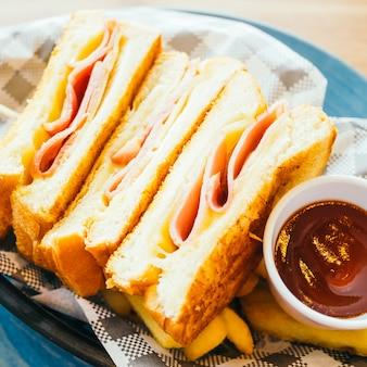 Sandwich mit Schinkenkäse und Pommes frites und Tomatensauce