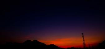 Satellitenschüssel und Kommunikationsturm über Sonnenuntergang.