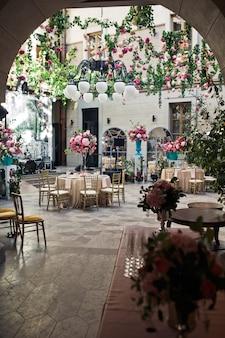 Schauen Sie aus der Ferne im Hinterhof mit Blumen zum Hochzeitsessen verziert