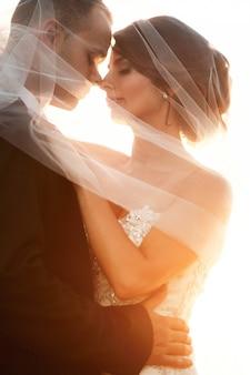 Schleier bedeckt atemberaubende Braut und Bräutigam umarmt vor goldenen Abendsonne