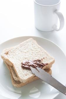 Schokoladencreme mit geschnittenem Brot auf weißem Teller und rosa Stoff auf weißem Hintergrund