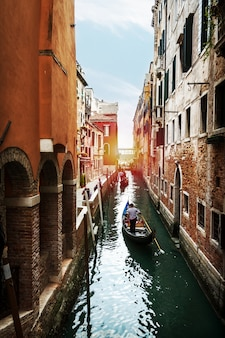 Schöne Aussicht auf den venezianischen Wasserkanal mit Gondolier und Boot. Venedig, Italien.