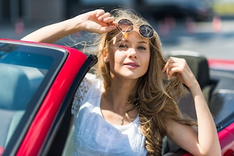 Schöne blonde Mädchen in einem umwandelbaren roten Auto. Sonniger Tag