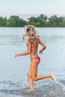 Schöne blonde Mädchen läuft am Strand