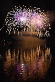 Schöne bunte Feuerwerk auf der Wasseroberfläche mit einem sauberen schwarzen Hintergrund. Fun Festival und internationaler Wettbewerb von Feuerwehrleuten aus aller Welt Ignis Brunensis 2017. Brno Dam - Tschechische Republik.