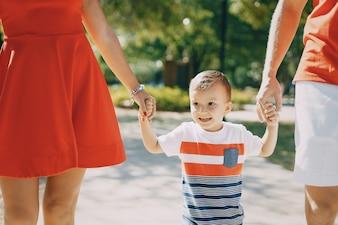 Schöne Familie in rot zu Fuß die Straße und den Park