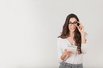 Schöne Frau, die eine Agenda und berühren ihre Brille