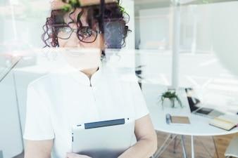 Schöne geschäftsfrau posiert mit digitaler tablette beim stand im büro.
