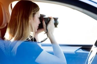Schöne junge Frau, die Fotos vom Auto macht.