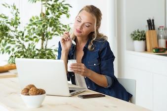 Schöne junge Frau, die ihren Laptop verwendet und Joghurt zu Hause isst.