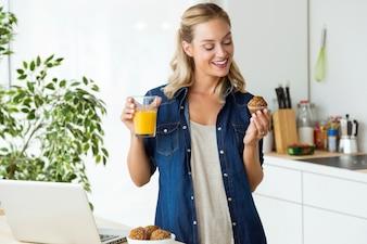 Schöne junge Frau, die in der Küche frühstückt.