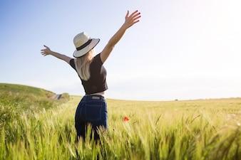 Schöne junge Frau, die Sommer auf einem Gebiet genießt.