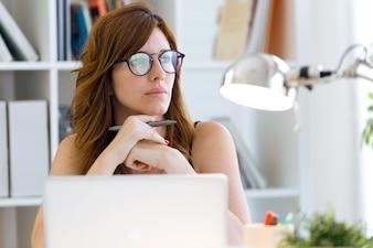 Schöne junge Frau, die zu Hause mit ihrem Laptop arbeitet.