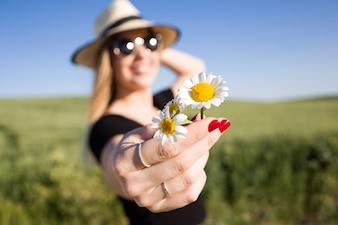 Schöne junge Frau mit Blumen Sommer auf einem Feld genießen.
