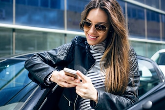 Schöne junge Frau mit ihrem Handy im Auto.