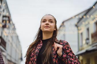 Schöne junge glückliche Brünette Mädchen mit langen Haaren posiert im Freien. Straßenfoto, Porträt, Nahaufnahmen.