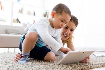 Schöne junge Mutter und ihr Sohn mit digitalen Tablette zu Hause.