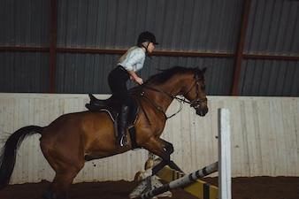 Schöne Mädchen reiten ein Pferd