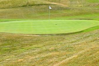 Schöner Golfplatz an einem sonnigen Sommertag. Loch mit einer Fahne. Beliebte Outdoor-Sport
