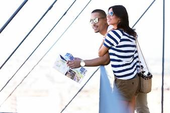 Schönes junges touristisches Paar in der Stadt, die eine Karte hält.