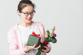 Schoss im Studio der jungen asiatischen Frau mit einem Weihnachtsgeschenk