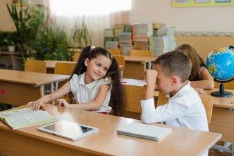 Schulkinder sitzen am Schreibtisch sprechen