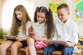 Schulkinder sitzen auf Bank halten Gadgets