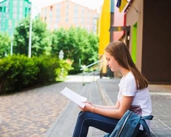 Schulmädchen lesen Buch auf Stufen