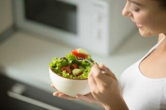 Schüssel frischen grünen Salat halten in weiblichen Händen