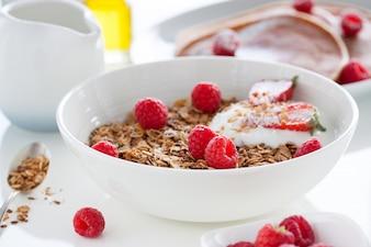 Schüssel mit Joghurt, Müsli und Himbeeren