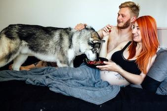 Schwangere Paar mit Hund auf dem Bett