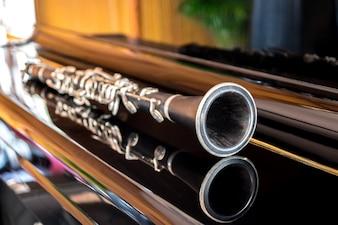 Schwarze Klarinette liegt auf dem Klavier