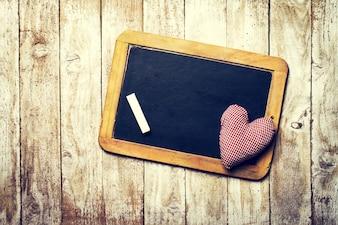 Schwarze Tafel mit einem Plüsch-Herz