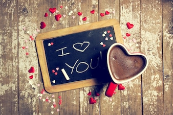 Schwarze Tafel mit kleinen Herzen, die um und eine Tasse Schokolade