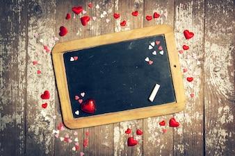 Schwarze Tafel mit kleinen Herzen, die um