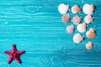 Seashells und rote Seesterne auf blauem Holz Hintergrund