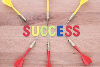 Sechs Dart laufen zum Erfolg auf Holzhintergrund