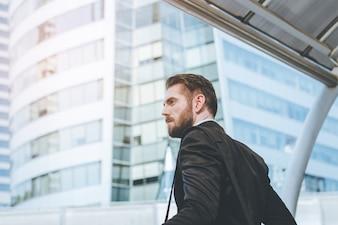 Seitenansicht des Erfolgs Geschäftsmann Blick auf moderne Gebäude mit Kopie Raum